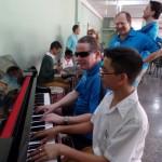 Tandemfahrer und Blindenschüler am Klavier