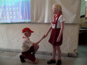 Ein Blindenschüler in Uniform knieht vor einer Mitschülerin. Hält er um ihre Hand an?