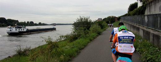 Auf dem Rhein ein Schiff, auf dem Fahrradweg daneben Teilnehmer des Tandem-Camps